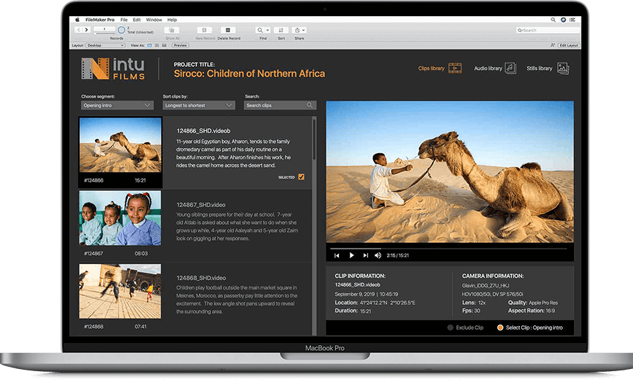 A MacBook Pro showing a custom app built in FileMaker Pro advanced. The custom app is a content library built for a film studio. It is displaying a database record of a video containing a young boy feeding a dromedary camel